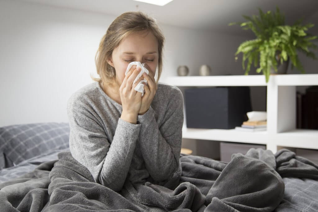 sick woman sitting bed blowing nose with napkin 1