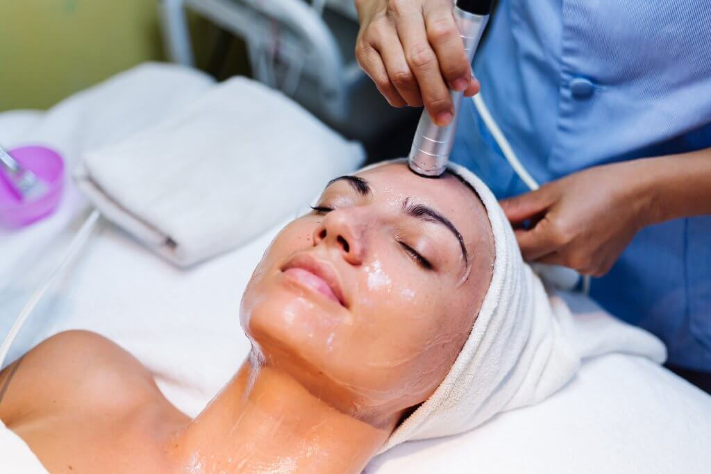 young woman lying cosmetologist s table during rejuvenation procedure